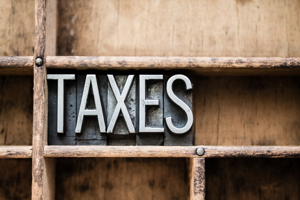 "The word ""TAXES"" written in vintage metal letterpress type in a wooden drawer with dividers."